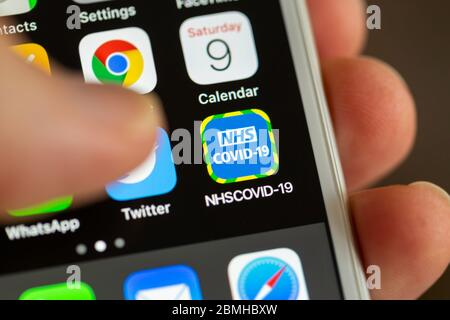 BATH, UK - MAY 9, 2020 : Close-up of the NHS COVID-19 contact tracing app on an iPhone screen with a thumb hovering above it. - Stock Photo