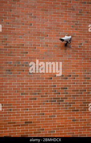 Surveillance video camera is mounted to a brick wall ...