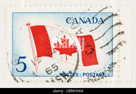 SEATTLE WASHINGTON - May 8, 2020: Close up of 1965 Canada maple leaf flag stamp commemorating the inaugeration of the National Flag. Scott # 439. - Stock Photo