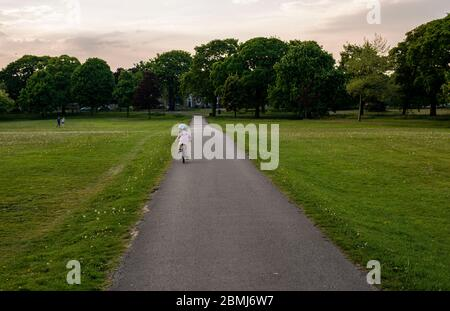Harrogate, North Yorkshire, UK, 9th May 2020.  A child cycles away in the empty Stray park in the centre of the town. Credit: Ernesto Rogata/Alamy Live News. - Stock Photo