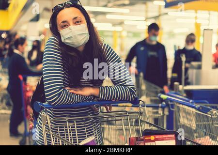 young woman wearing a hygiene protective mask over her face while walking at the crowded shopping mall. Covid19 influenza in crowded place. woman - Stock Photo
