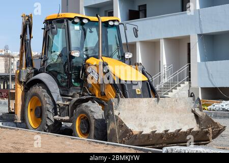 Kharkiv, Ukraine, March 29, 2020: Excavator JCB parked outside. The dirty yellow tractor at the construction site. European vehicle, bulldozer with bu - Stock Photo