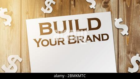 Build Your Own Brand words on a page and paper dollar signs around on wooden table. Branding rebranding marketing business concept
