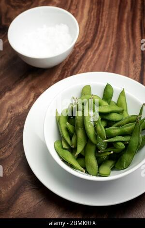 organic edamame beans snack in bowl on table with sea salt - Stock Photo