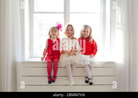three beautiful little girls in red and white dresses sitting by the window