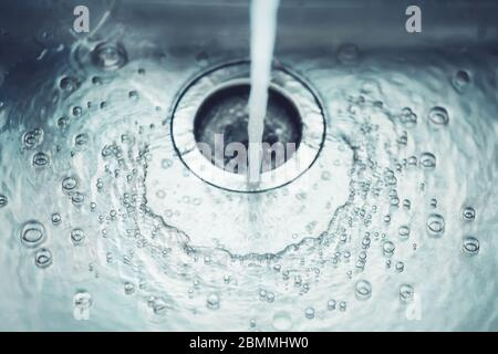 In the metal sink in the kitchen, water flows from the tap, which bubbles and flows into the drain hole. - Stock Photo