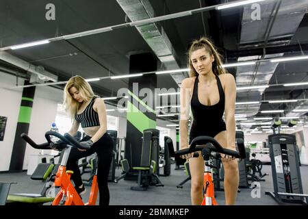 Full length view of two young girls in sporty outfit doing spinning in an empty gym. Two women exercising on bicycle in fitness center - Stock Photo