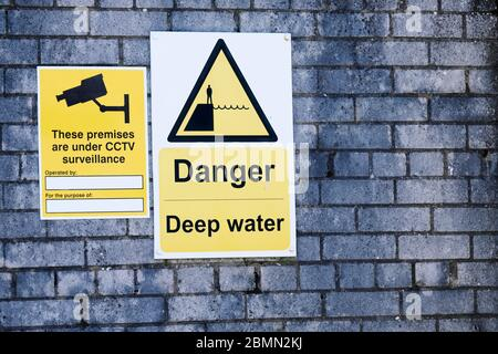 Deep water danger yellow symbol sign on sea wall - Stock Photo