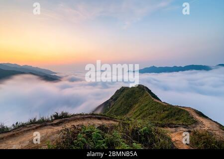 Ta Xua is a famous mountain range in northern Vietnam. All year round, the mountain rises above the clouds creating cloud inversions. - Stock Photo
