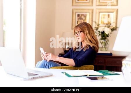 Shot of confident mature woman text messaging while sitting behind her laptap in the living room and working from home. Home office. - Stock Photo