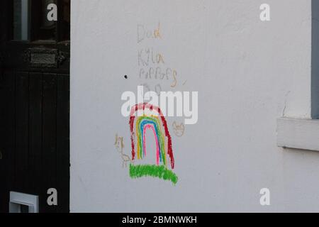 Huddersfield, UK - May 4 2020: A child's drawing of a rainbow in crayon on the side of a house in West Yorkshire.