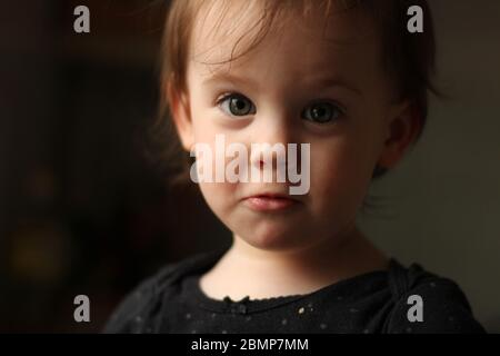 Close-up portrait of a little cute white baby with a dirty face in soft light and blurry background