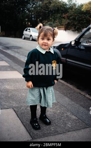 Young primary school child / girl in a residential street, smiling in a green school uniform, waiting to go to school, UK - Stock Photo