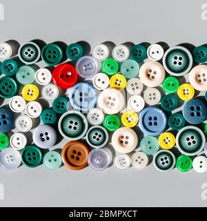 Colorful mixed sewing buttons on grey background, flat lay. Items for sewing clothes.  Top view, square cropping. - Stock Photo