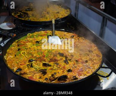 Paela dish in large cast iron pan. Spanish cuisine restaurant meal preparation. Real life scene - Stock Photo
