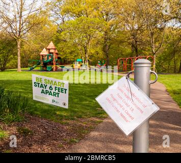 Signs posted in front of the Bartlett playground in Schenley Park stating that it is closed due to Covid-19 and to social distance, Pittsburgh, PA, US - Stock Photo