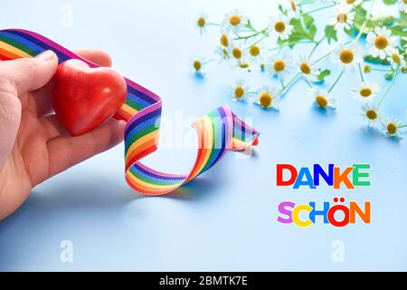Red heart and rainbow ribbon. Rainbow text 'Danke shon' in German language means 'Thank you' in English. Symbols of public support of doctors and nurs - Stock Photo
