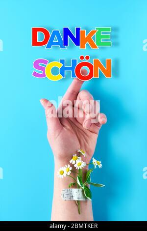 Text 'Danke shon' in German language means 'Thank you'. Rainbow ribbon in woman's hand. Chamomile flower and grass bouquet attached with medical aid p - Stock Photo