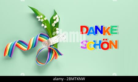 Text 'Danke shon' in German language means 'Thank you'. Rainbow ribbon, lily of the valley flowers. Bouquet attached to background with medical aid pa - Stock Photo