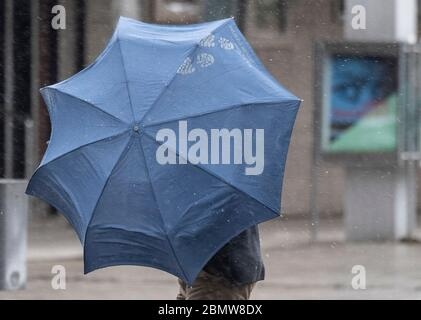 11 May 2020, Hessen, Frankfurt/Main: In gusts of wind and rain, a passer-by fights his way through the city centre with his stretched umbrella. The temperatures on this day in May have dropped to a fresh six degrees above zero. Photo: Boris Roessler/dpa