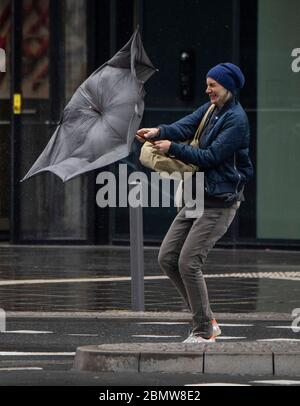 11 May 2020, Hessen, Frankfurt/Main: In gusts of wind and rain, a passer-by struggles through the city centre with her umbrella. The temperatures on this day in May have dropped to a fresh six degrees above zero. Photo: Boris Roessler/dpa
