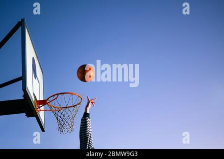 Street basketball ball player throwing ball into the hoop. Close up of hand, orange ball above the hoop net with blue sky in the background. Concept o