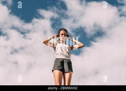 Low angle shot of a fitness woman adjusting her headphones before going for a morning run - Stock Photo