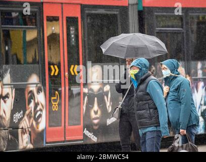 11 May 2020, Hessen, Frankfurt/Main: In gusts of wind and rain, passers-by wearing face masks walk through the city centre. The temperatures on this day in May have dropped to a fresh six degrees above zero. Photo: Boris Roessler/dpa