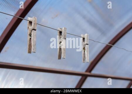 Three old wooden clothespins hang on a rope. Housekeeping equipment - Stock Photo