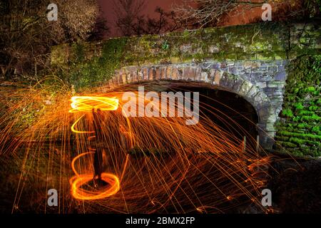 afire spinning with steel wool at an old disused railway bridge - Stock Photo