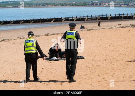 Portobello, Scotland, UK. 11 May 2020. Police patrolling promenade and beach at Portobello this afternoon in warm sunny weather. They spoke to the public who were sitting on the beach or on sea wall asking them to keep moving. Iain Masterton/Alamy Live News - Stock Photo