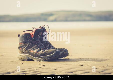 Close up of men's abandoned walking boots isolated on sand of empty, deserted UK beach in summer sunshine. Enjoying beach combing & paddling in sea. - Stock Photo