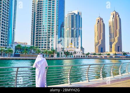 DUBAI, UAE - MARCH 2, 2020: The Emirati man, weared in traditional white kandura (thobe) and ghutra (headscarf) stands at the baluster of Dubai Marina - Stock Photo