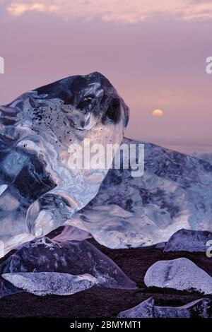 Striking ice formations are staged by evening clouds lit by a cloud cover in red and yellow shades, the setting sun is visible - Location: Iceland, so - Stock Photo