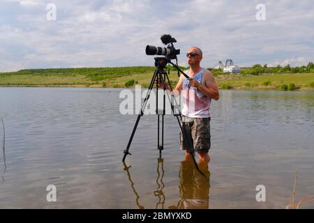 A photographer standing in shallow water, to get the angle that wasn't possible from the edge of the lake at RSPB St Aidan's - Stock Photo