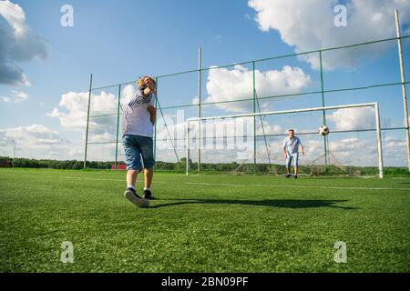 Happy father and excited son playing together soccer on a green football field running on grass kicking the ball in. Dad and boy relationship and - Stock Photo