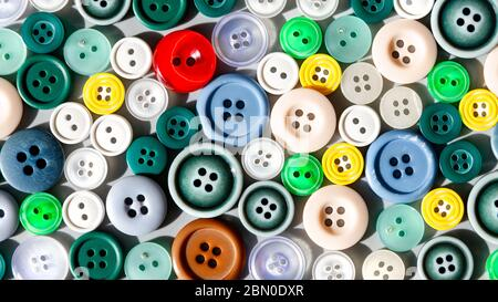 Colorful mixed sewing buttons lit by sunlight, flat lay. Items for sewing clothes.  Top view - Stock Photo