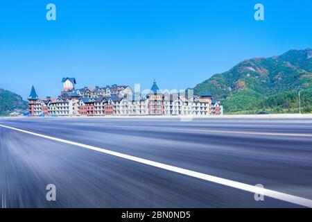 The empty car-free highway and the European-style building castle, in the distance are green mountains.