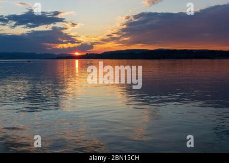 Stunning sunset on the shores of the Upper Zurich Lake (Obersee), near Rapperswil, St. Gallen, Switzerland - Stock Photo