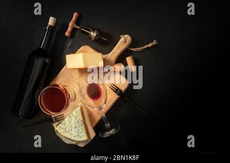 Wine and cheese tasting, top shot on a black background with a place for text, with a cork, corkscrew, and a bottle - Stock Photo