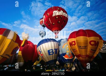 Early morning mass ascent of colourful hot air balloons at the Bristol International Balloon Fiesta, Ashton Court, Bristol, England, UK
