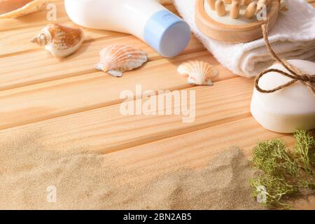 Thalassotherapy products for body treatment on wooden slats table decorated with seaweed shells and sand. Elevatedview. Horizontal composition. - Stock Photo