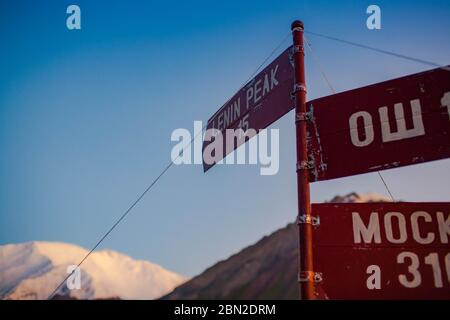 Close-up of red sign for the Lenin peak. Trans-Alay Range. Pamir Mountain System. Blue sky. - Stock Photo