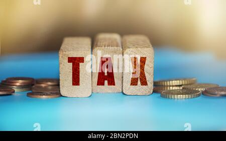 Tax word on wooden blocks and coins on table. Fonancial business legislation concept