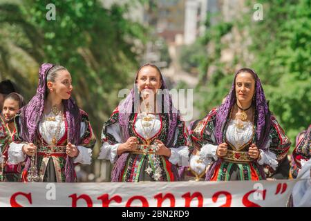 Traditional costume, portrait of three young women in traditional costume during the grand parade of the Cavalcata festival in Sassari, Sardinia - Stock Photo