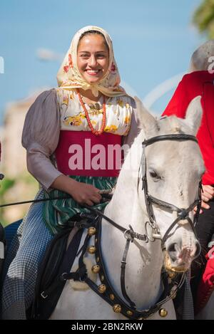 Sardinia, portrait of a young woman in traditional costume and riding her horse in the grand procession of the Cavalcata festival, Sassari, Sardinia. - Stock Photo