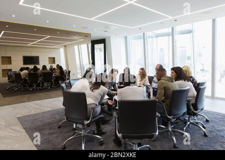Business people meeting in circle in conference room - Stock Photo