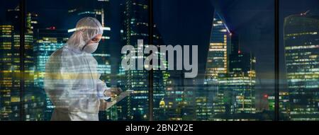 Male scientist in clean suit working late in city window - Stock Photo