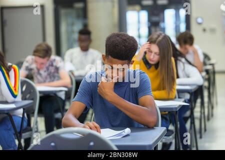 Focused high school boy student taking exam at desk in classroom - Stock Photo