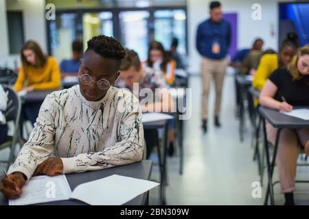 Focused high school boy student taking exam at desk - Stock Photo